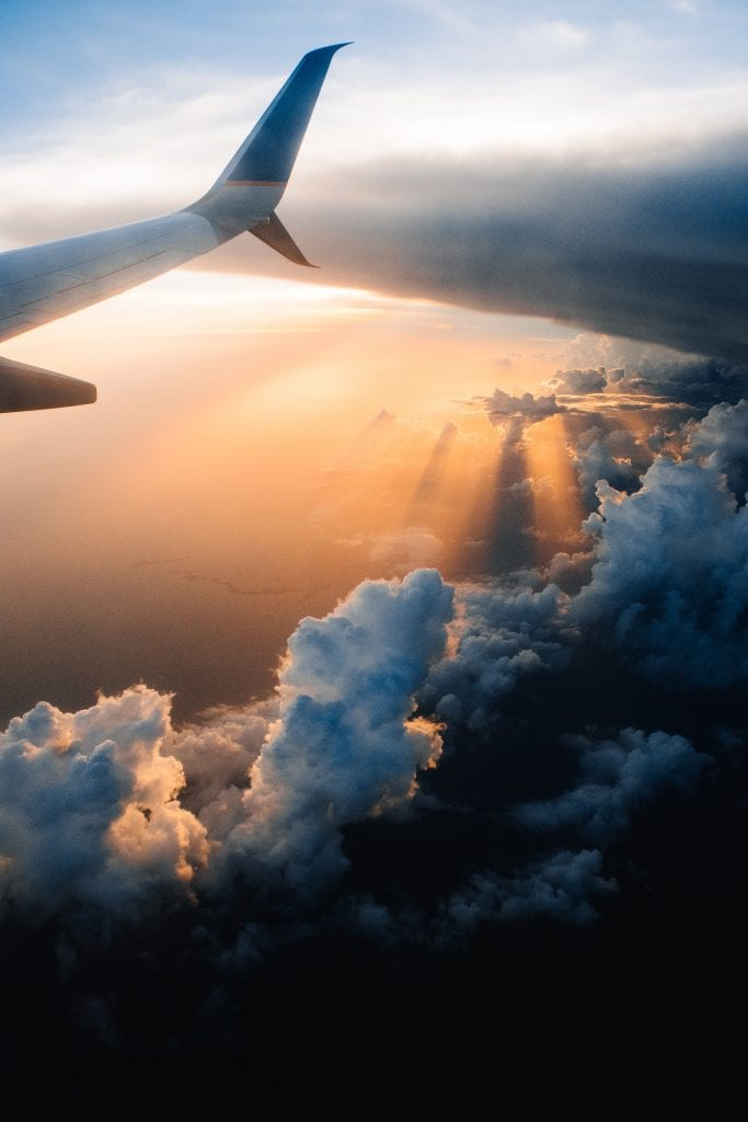 Plane wing with clouds and sun